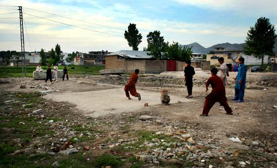 A group of boys plays cricket near the site of the demolished compound of Osama bin Laden
