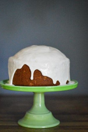 A round cake with thick white frosting dripping down the sides.