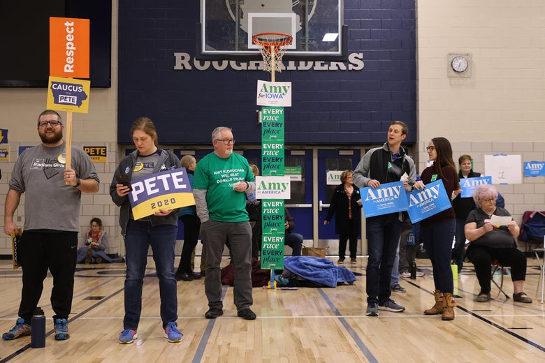 People stand in a gym underneath a basketball hoop, carrying signs for different candidates.