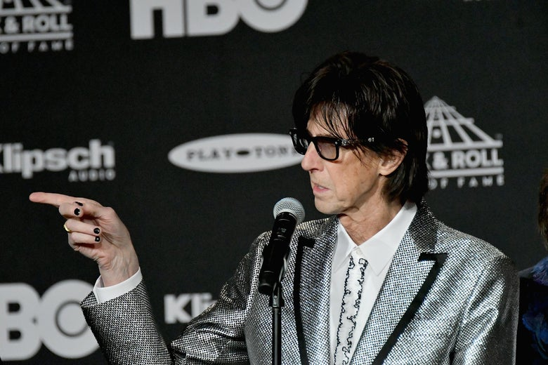 Ric Ocasek of the Cars points his finger at something off-camera at the Rock and Roll Hall of Fame.