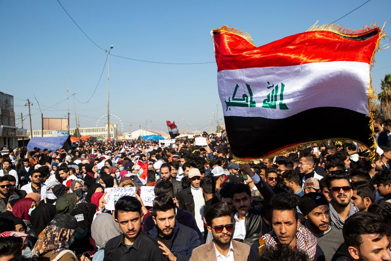 Iraqi demonstrators wave the national flag during an anti-government rally in the southern city of Basra.
