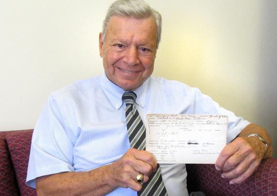 Peter Vallone holding the report card of his mother, Leah Palmigiano Vallone.