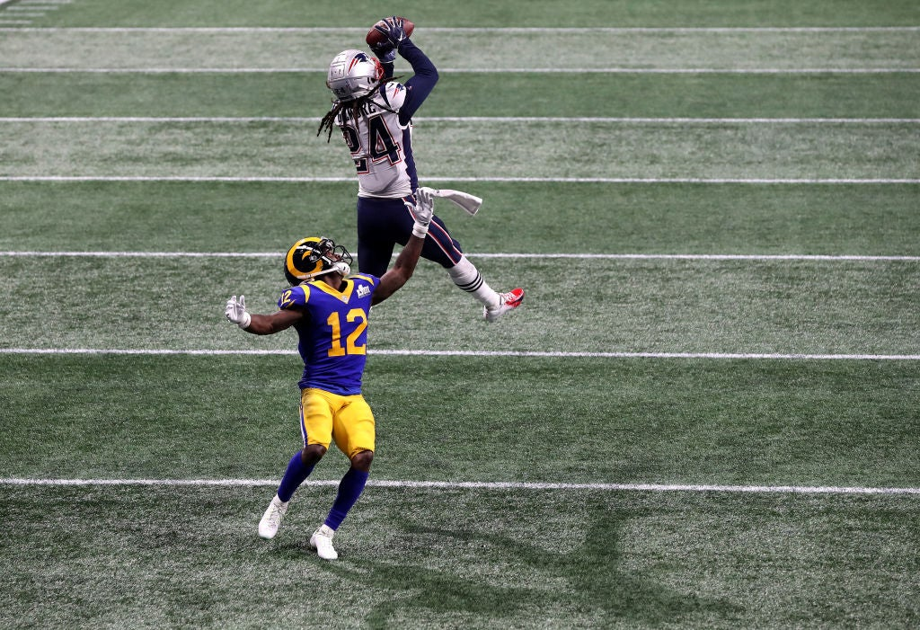Gilmore, leaping, makes the interception as Brandin Cooks turns helplessly to watch.