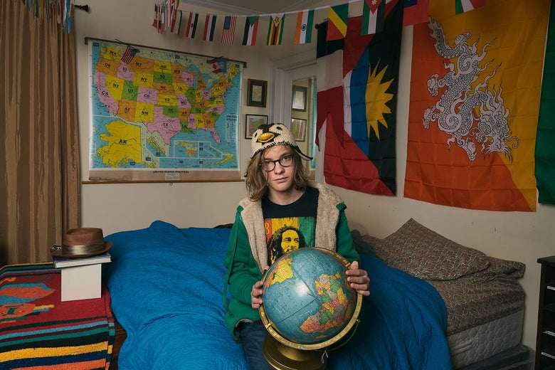 Satchel, holding a globe in his bedroom, 10th grade.