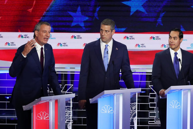 De Blasio speaking next to Ryan and Castro on the debate stage.