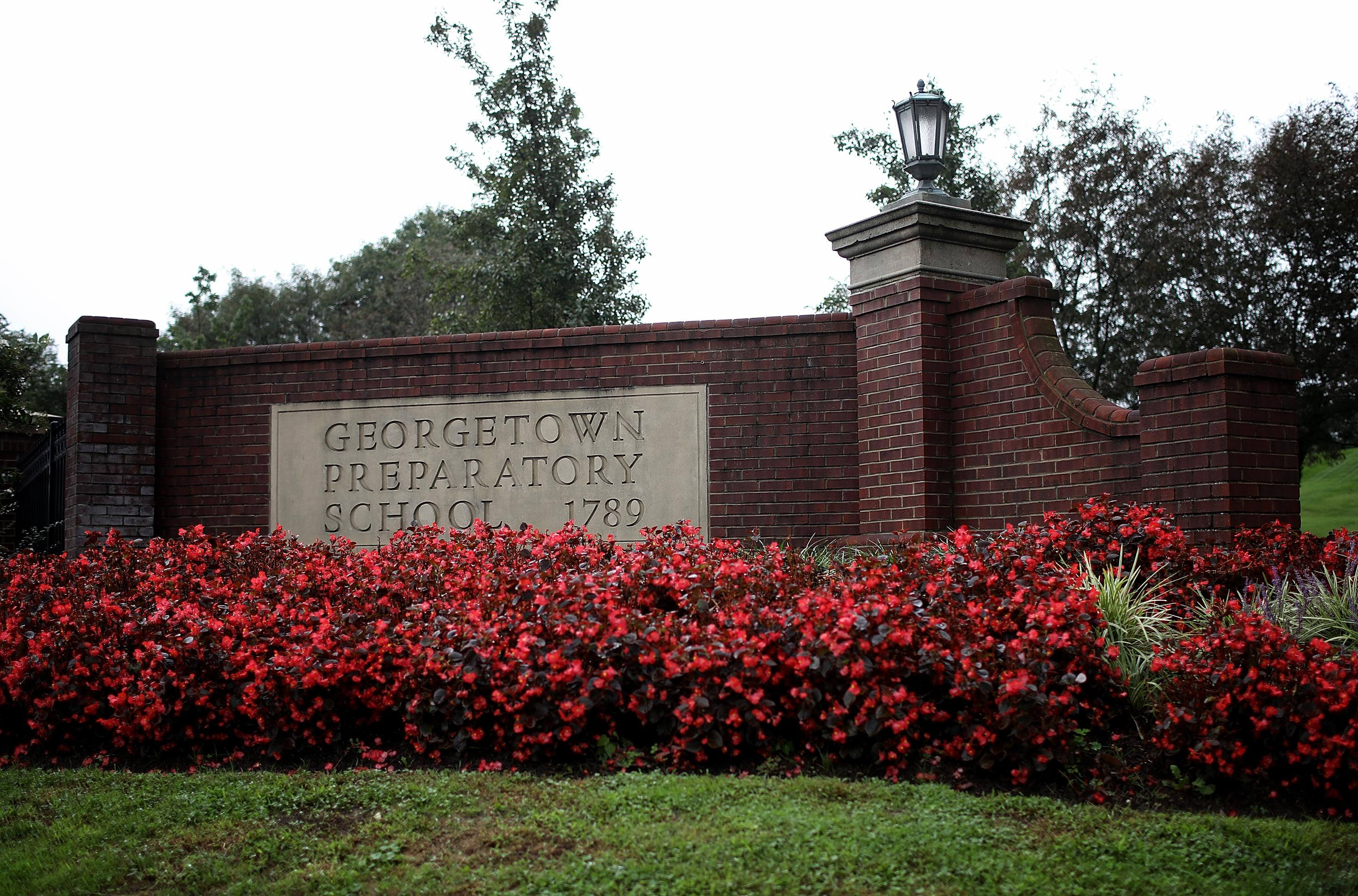 A sign for the Georgetown Preparatory School surrounded by red flowers.