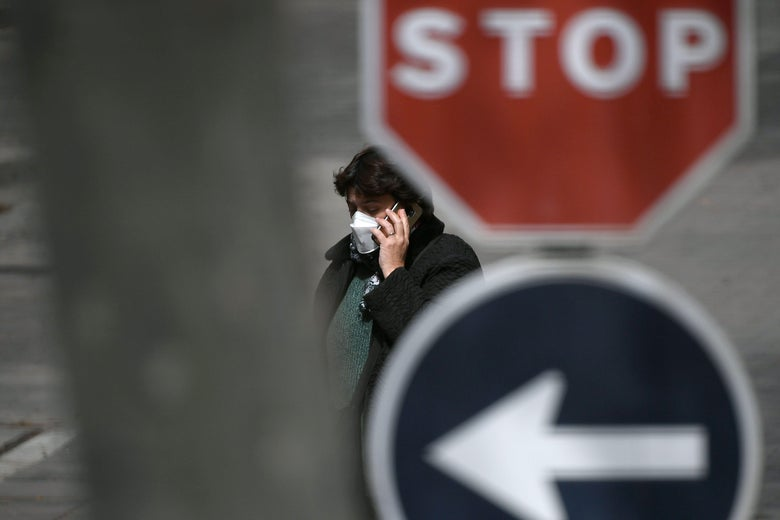 A woman wearing a face mask talks on her phone as she walks by a stop sign.