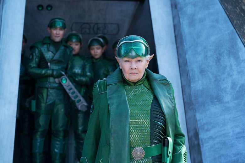 Judi Dench wears a green helmet, coat, and belt. She has pointed ears.
