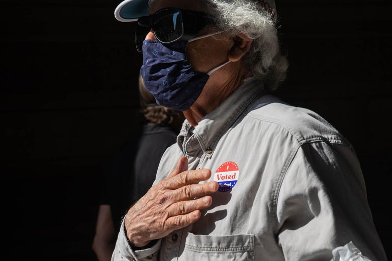 "A man in a hat, mask, and sunglasses holds his hand over an ""I Voted"" sticker on his shirt."
