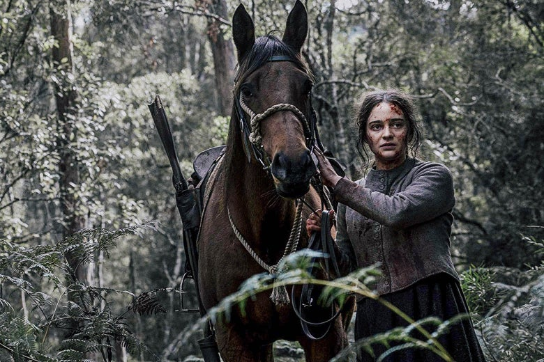 In this still from The Nightingale, a bloodied Aisling Franciosi leads a horse through a forest.