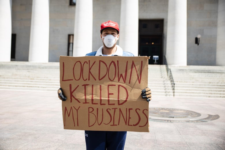 "A protester wearing a MAGA hat and a medical mask holds a sign that says ""Lockdown killed my business"""