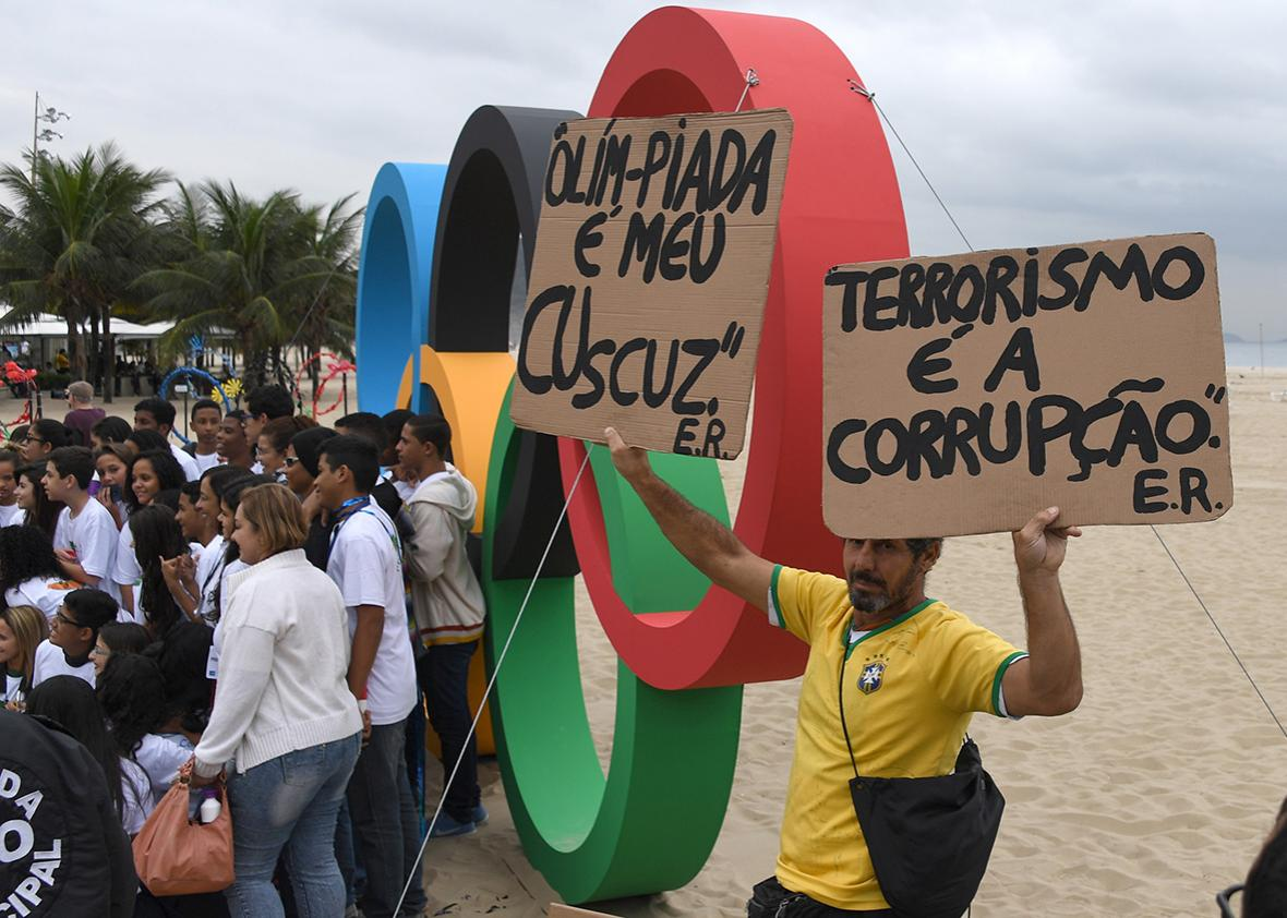 Activists protest against corruption in front of Olympic rings made out of recycled material inaugurated in Copacabana Beach on July 21, 2016.