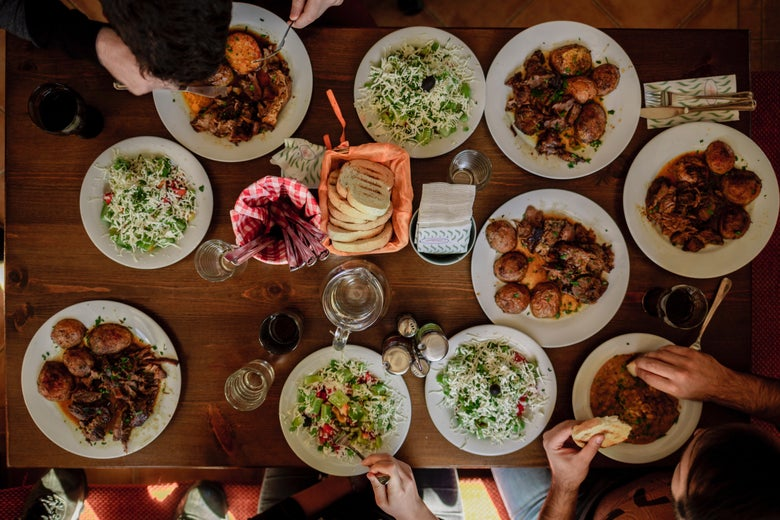 A table full of various dishes is photographed from above. Multiple people enjoy potatoes, salads, and bread in close proximity to one another.