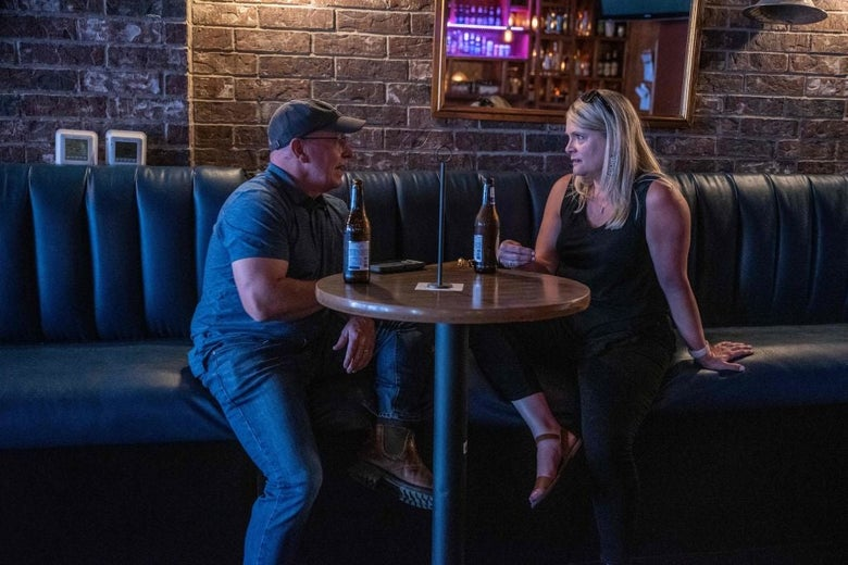 A man and a woman, neither wearing a mask, speak to each other at a bar table indoors