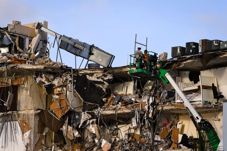 Rescue workers on a green crane stand above the wreckage of a partially collapsed building in Surfside north of Miami Beach, Florida.