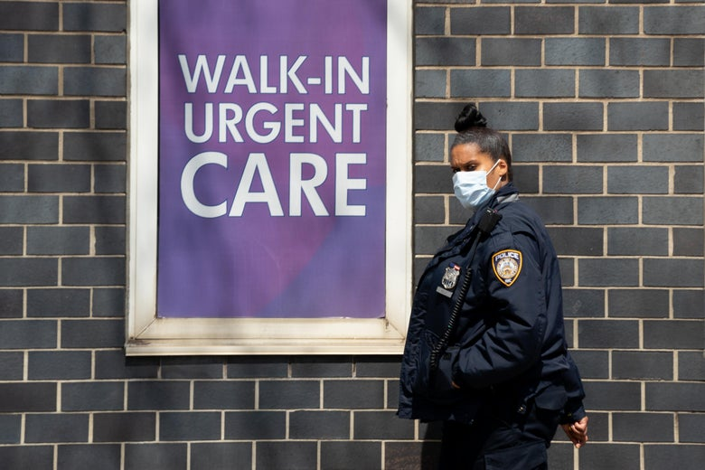 "A police officer in a face mask walks near a sign that says ""Walk-In Urgent Care."""