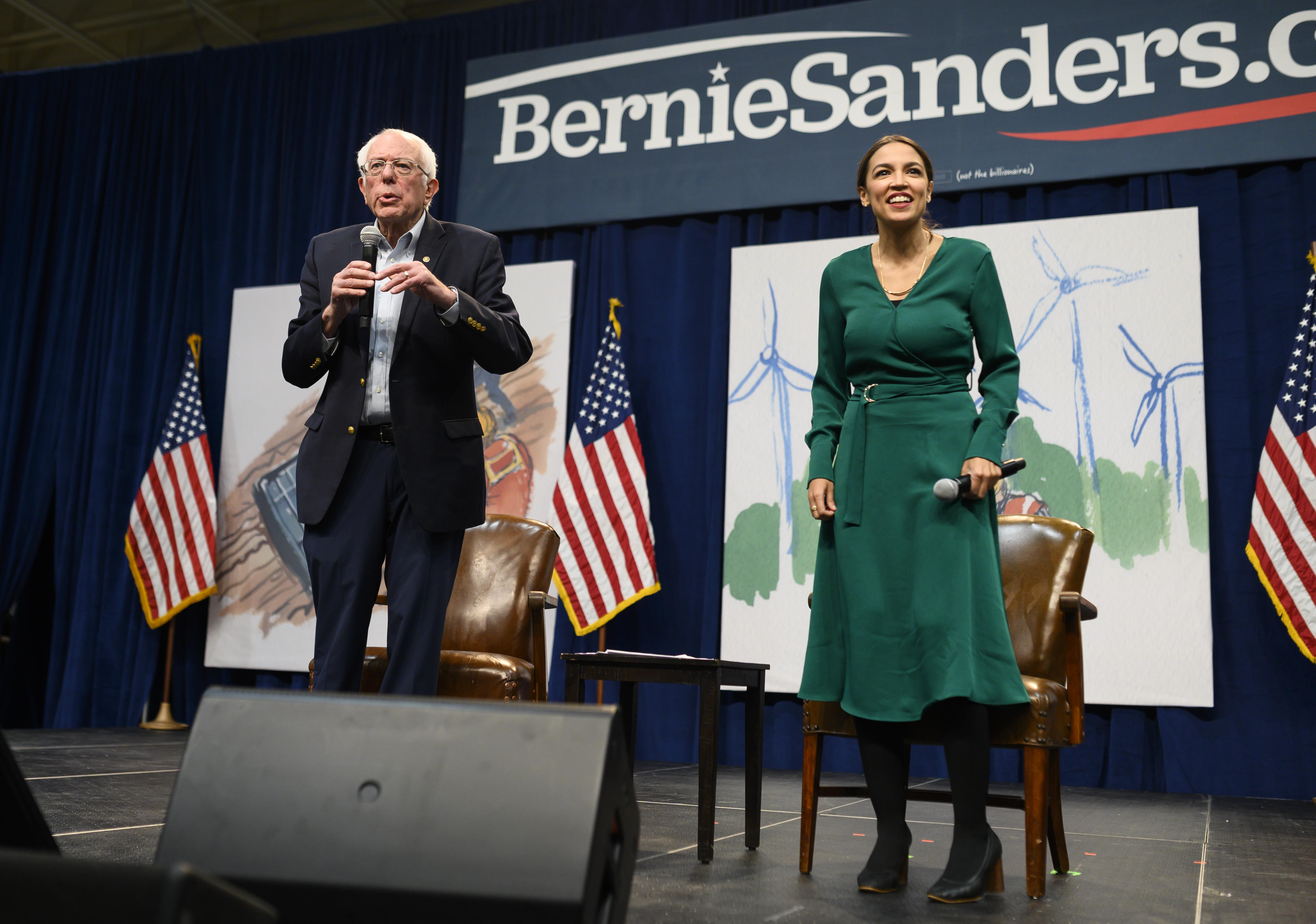"""Democratic presidential candidate Bernie Sanders and Rep. Alexandria Okazio-Cortez field questions from members of the audience at the Drake University Summit on Climate Change on November 9, 201<div class=""""e3lan e3lan-in-post1""""><script async src=""""//pagead2.googlesyndication.com/pagead/js/adsbygoogle.js""""></script> <!-- Text_Image --> <ins class=""""adsbygoogle""""      style=""""display:block""""      data-ad-client=""""ca-pub-7122614041285563""""      data-ad-slot=""""2268374881""""      data-ad-format=""""auto""""      data-full-width-responsive=""""true""""></ins> <script> (adsbygoogle = window.adsbygoogle 