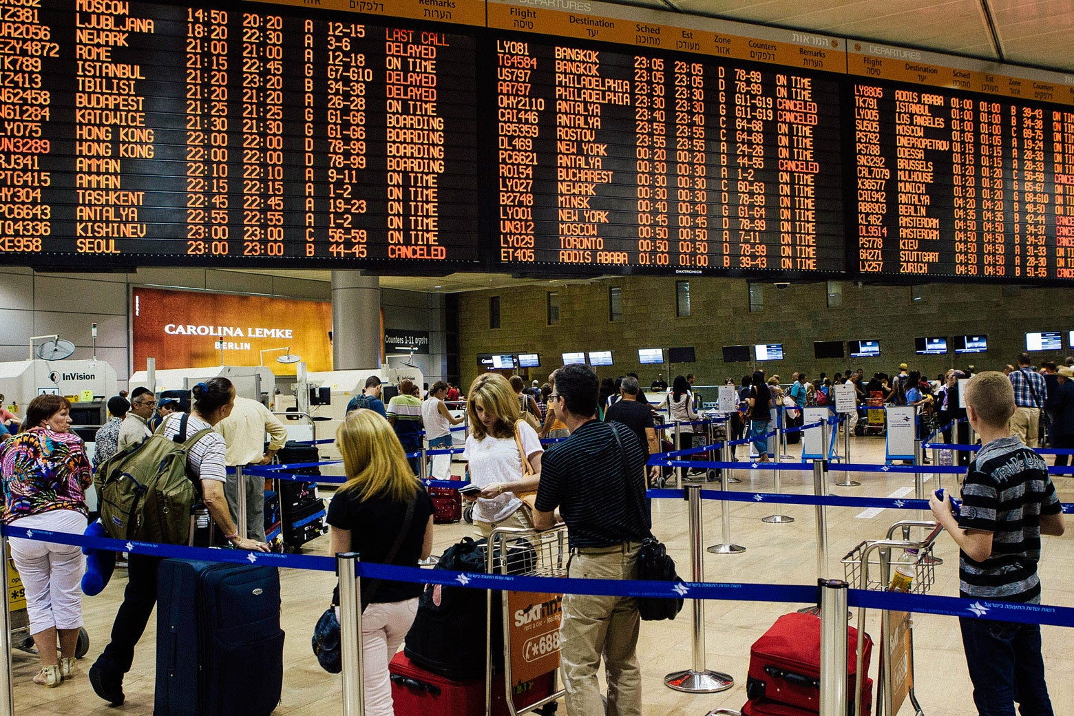 People stand in line below a departures and arrivals board.