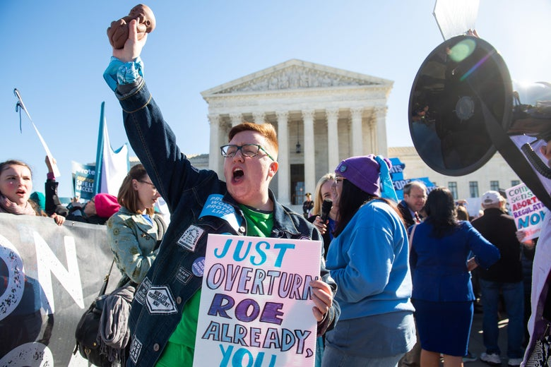 A protester holding a sign urging the Supreme Court to overturn Roe v. Wade.