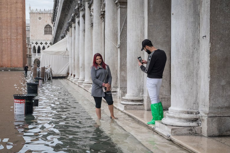 Tourists take pictures in a flooded St. Mark's Square, Nov 17th 2019, Venice.