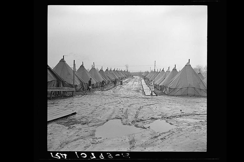 Tents line a muddy alley.