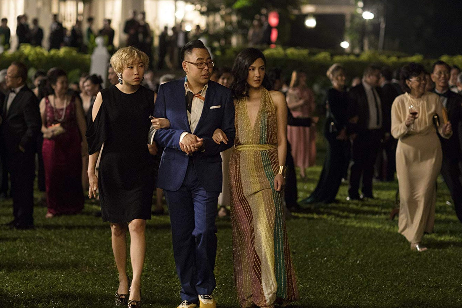 Awkwafina, Nico Santos, and Constance Wu wander the yard of a party in this still from Crazy Rich Asians