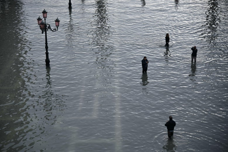 People take photos at the flooded St. Mark's Square.