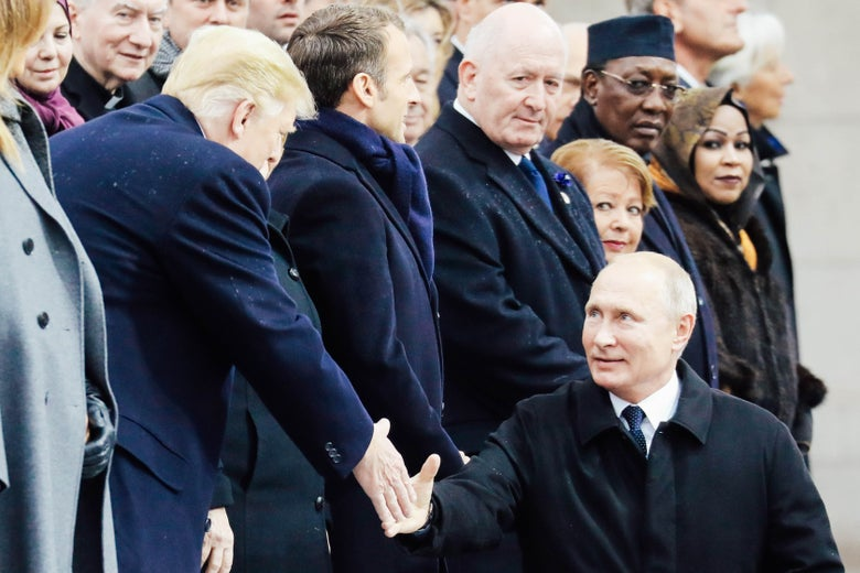 A standing President Donald Trump shakes hands with a seated Russian President Vladimir Putin at the Arc de Triomphe in Paris on Nov. 11.