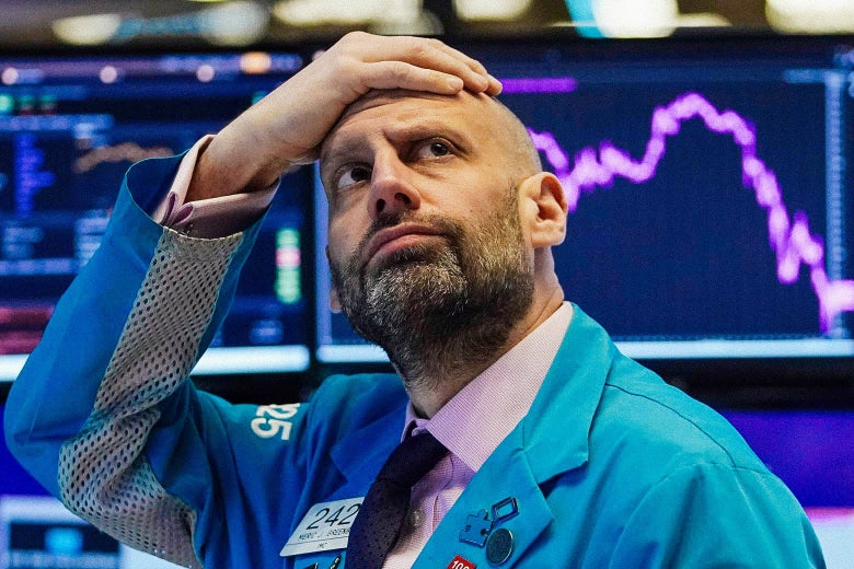 Meric Greenbaum puts his hand on his head in dismay, looking up at the board at the New York Stock Exchange on Monday.