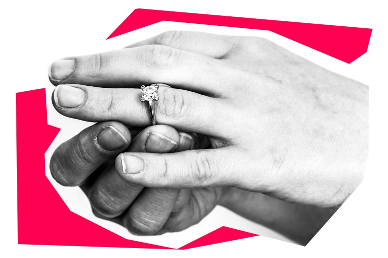 A hand with a wedding ring holds another hand.
