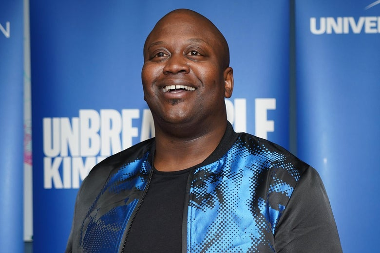 Tituss Burgess on a red carpet, smiling.