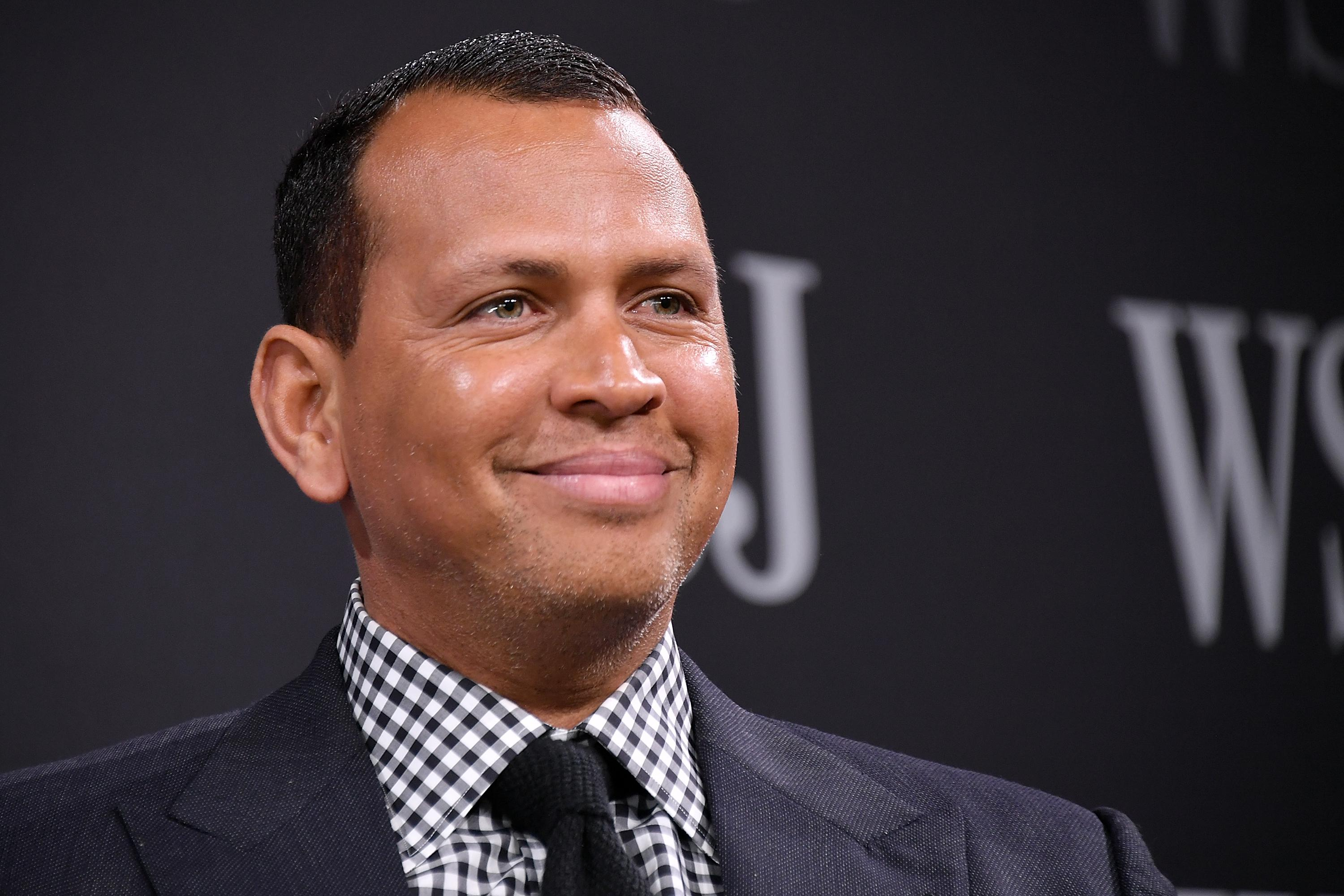 Alex Rodriguez smiles in a suit and tie while onstage at a Wall Street Journal event.