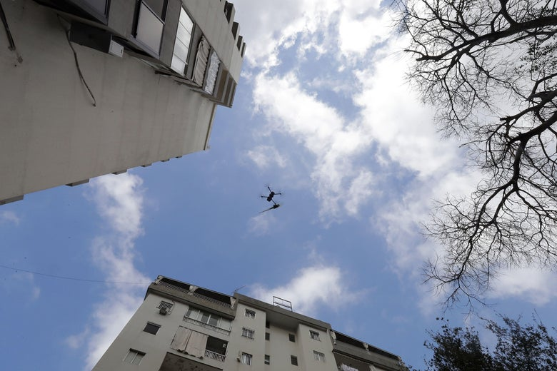 Low-angle shot of a drone flying between tall buildings toward a balcony. There is a rose attached to the drone.