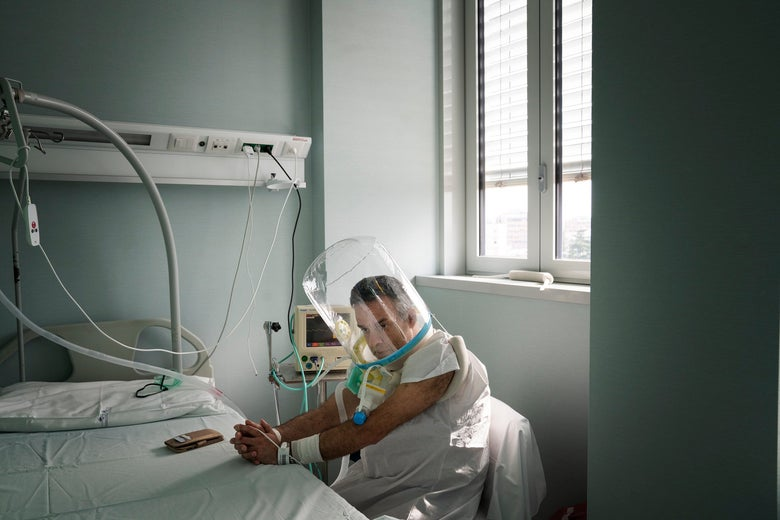 A man wearing an oxygen helmet sitting at his bedside at a hospital.