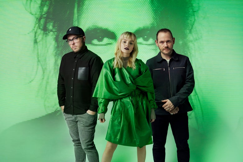 Three people—a man dressed in black with gray pants, a woman in a green dress with blonde hair, and a man in a navy jacket in black pants—stand in front of a green projection on the wall of a man holding his face.