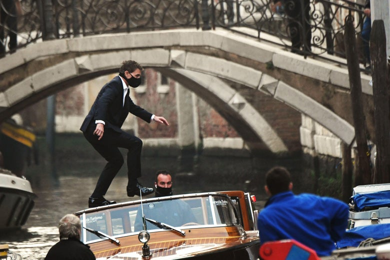 Tom Cruise, wearing a black mask, stands balancing on a taxi boat in a canal
