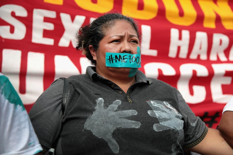 "A McDonald's worker stands in front of a protest sign with tape reading ""#MeToo"" over her mouth."