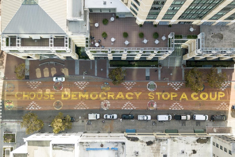 "An aerial view of a mural on a street that reads ""Choose Democracy Stop a Coup."""