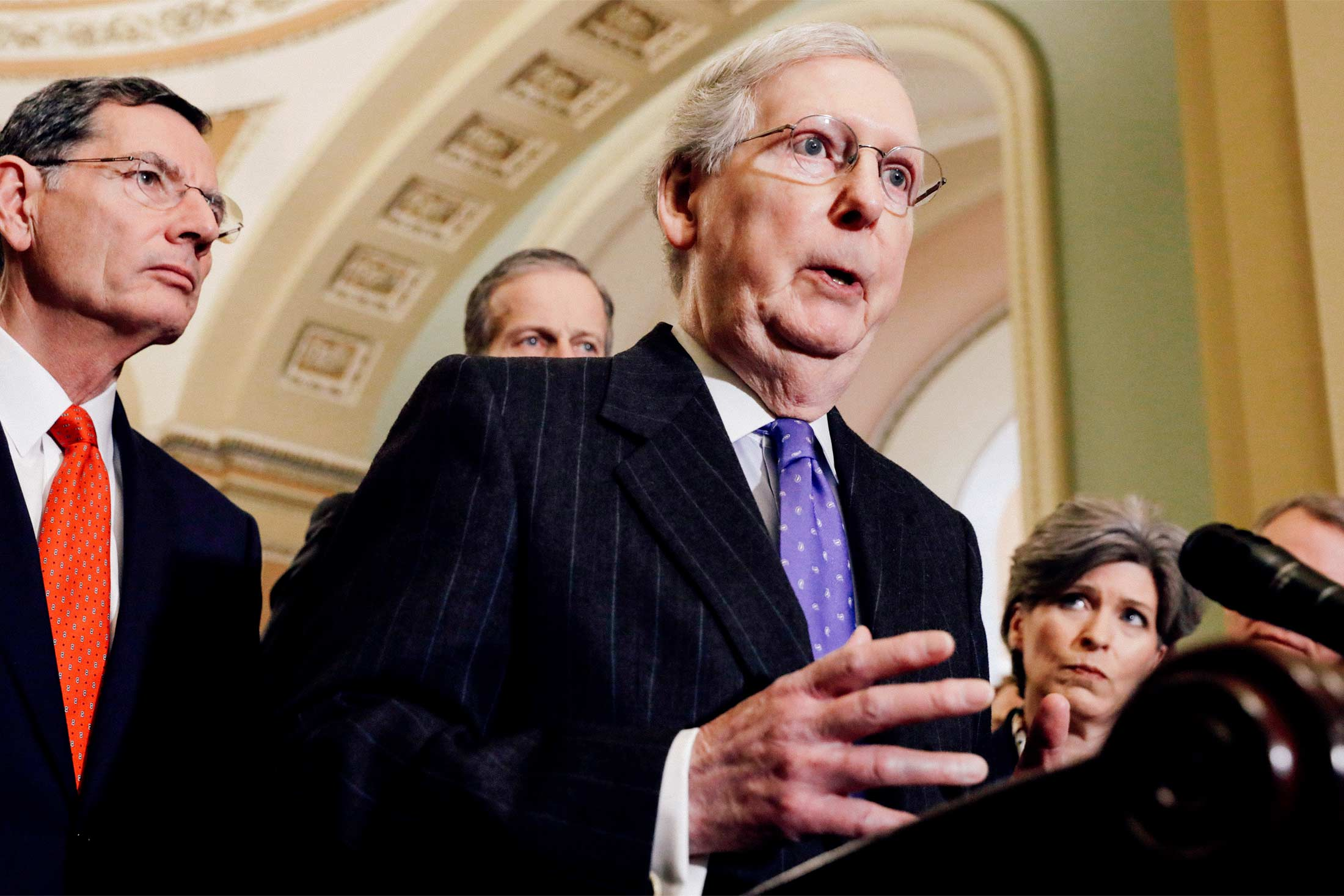 Mitch McConnell at a podium in the Capitol, surrounded by Republican senators and reporters.