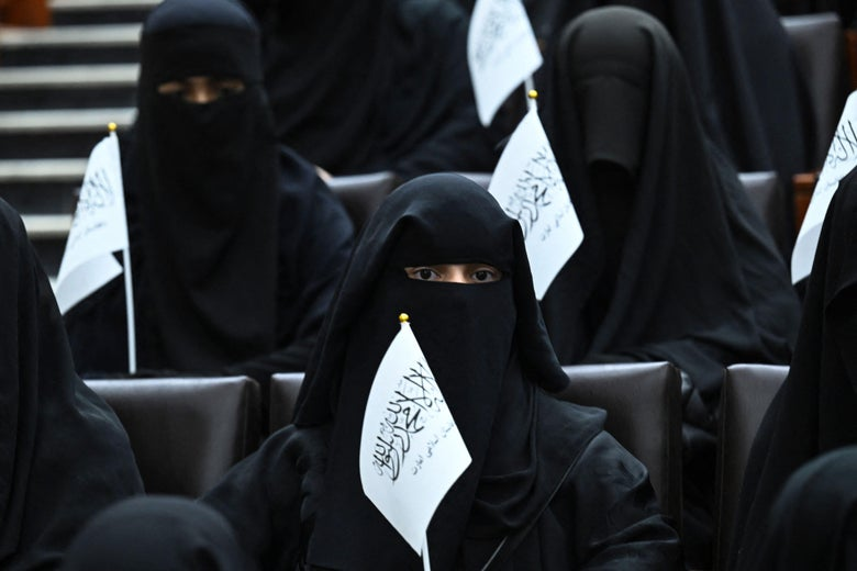 Veiled students hold Taliban flags as they listen a speaker before a pro-Taliban rally at the Shaheed Rabbani Education University in Kabul on September 11, 2021.