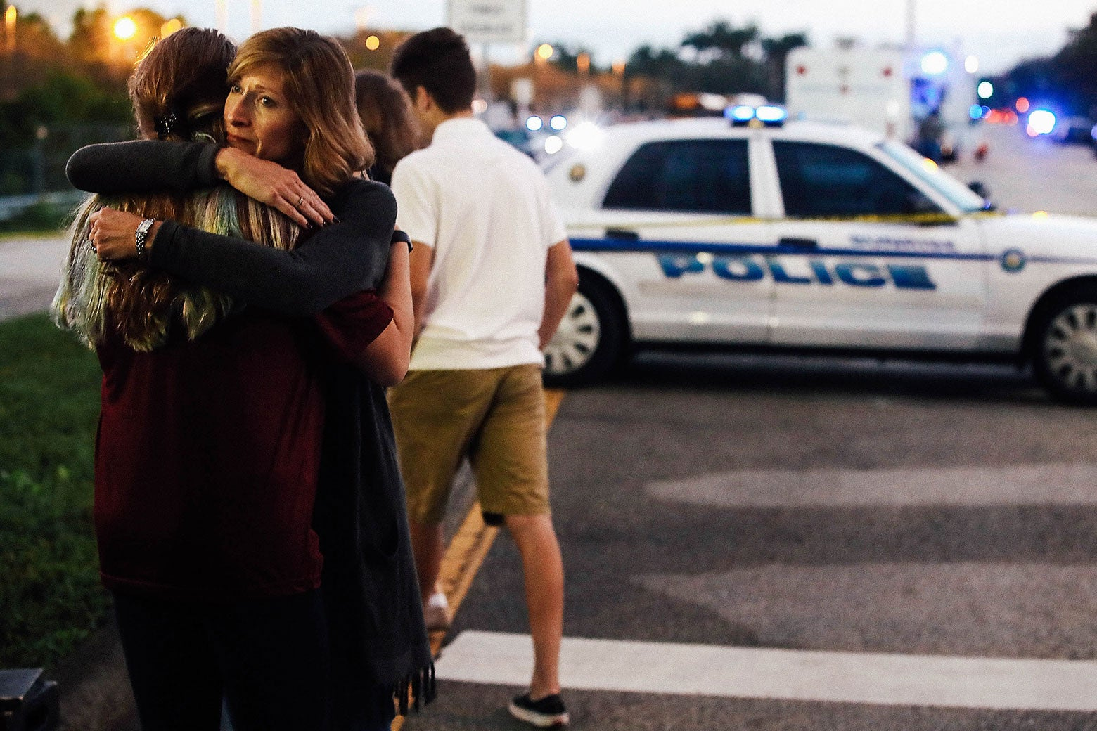 Kristi Gilroy hugs a young woman at a police checkpoint near Marjory Stoneman Douglas High School on Thursday in Parkland, Florida.