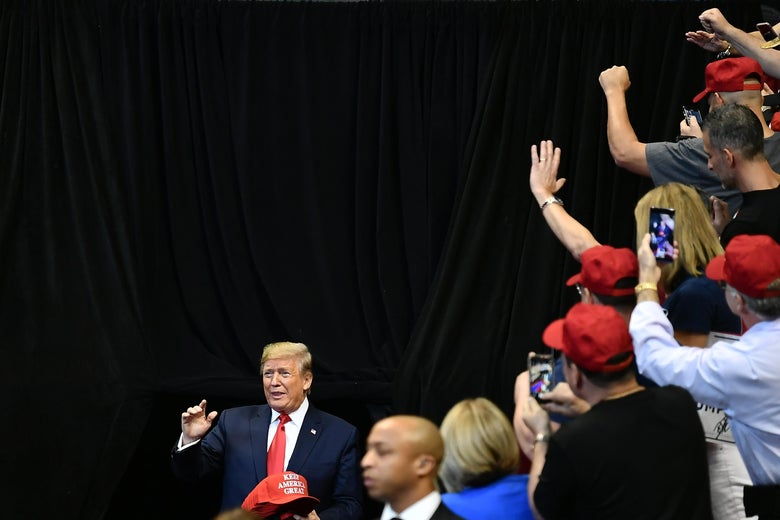 Donald Trump arrives at a rally as supporters in red hats take photos of him and cheer.