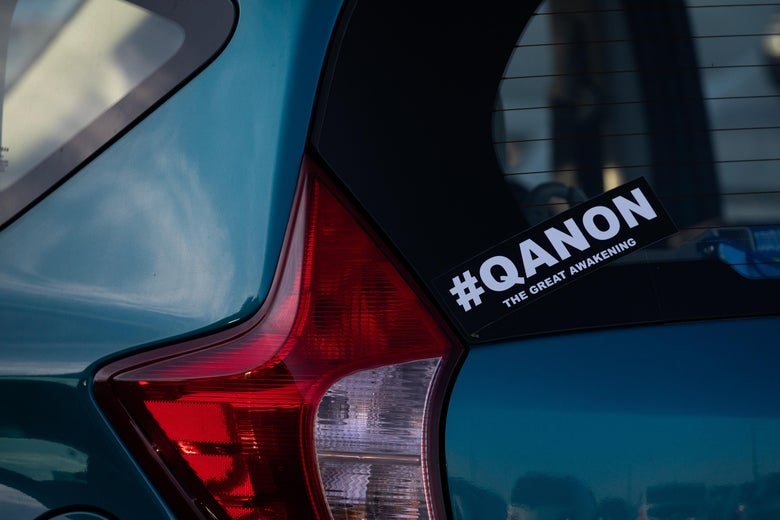 A bumber sticker on a car window says #QANON, the great awakening.
