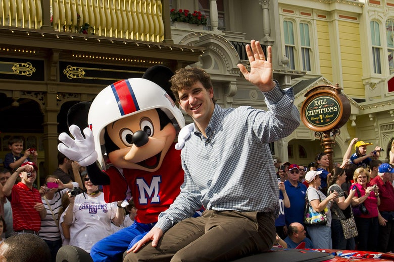 LAKE BUENA VISTA, FL - FEBRUARY 6:   In this handout image provided by Disney Parks, Super Bowl XLVI MVP and New York Giants quarterback Eli Manning takes a celebratory ride with Mickey Mouse on February 6, 2012 at the Magic Kingdom at Walt Disney World Resort in Lake Buena Vista, Florida.  The celebration at the theme park took place only one day after Manning led his team to a 21-17 victory over the New England Patriots in Super Bowl XLVI in Indianapolis.  Immediately following the game, Manning looked into TV cameras and shouted 'I'm Going to Disney World!'  He is the latest star in the famous Disney commercial series. (Photo by Matt Stroshane/Disney Parks via Getty Images)