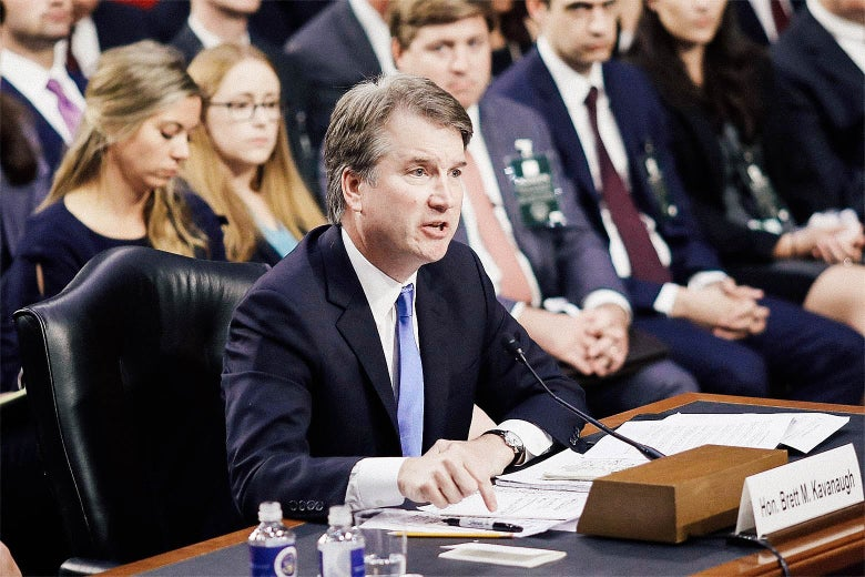 Kavanaugh points a finger toward the desk at which he's seated and speaking from in a confirmation hearing.