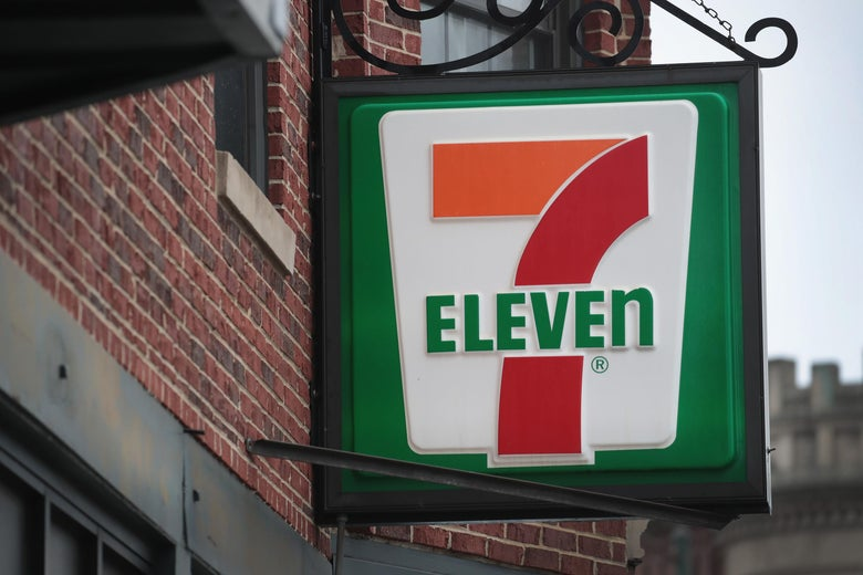 A 7-Eleven sign hanging outside the store.