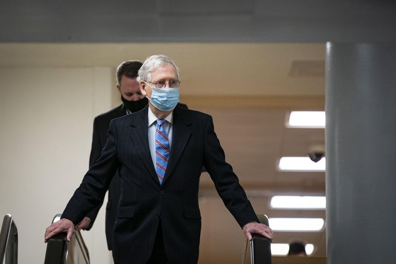 McConnell, wearing a mask, holds the handrails of an escalator down to the subway of the U.S. Capitol