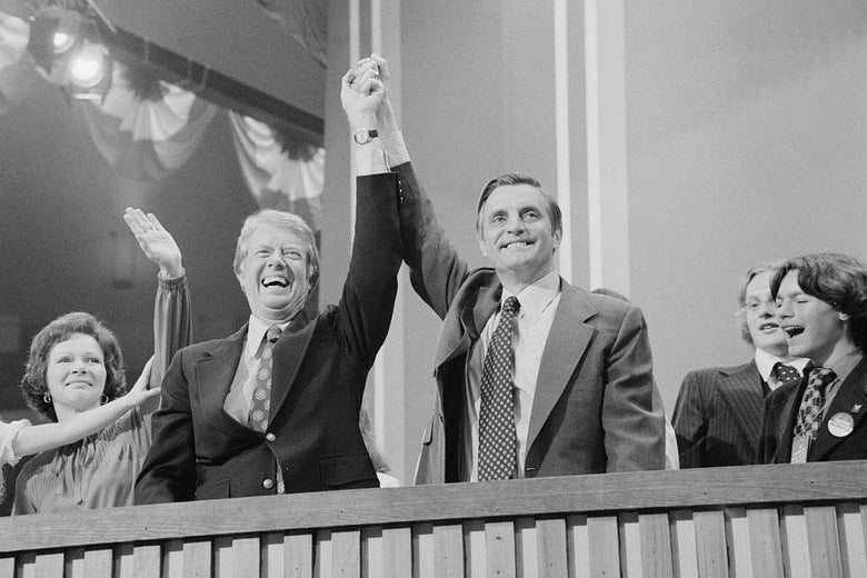 Carter and Mondale clasp hands at a stage while their families stand beside them.