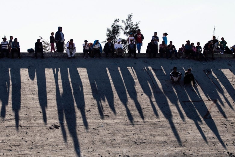 Migrants sitting on a concrete wall cast long shadows.