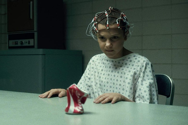 Millie Bobbie Brown in Stranger Things, wearing a complicated contraption on her head and crushing a Coke can with her mind.